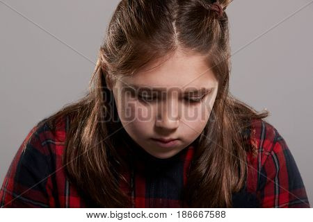 Ten year old girl looking down, head and shoulders