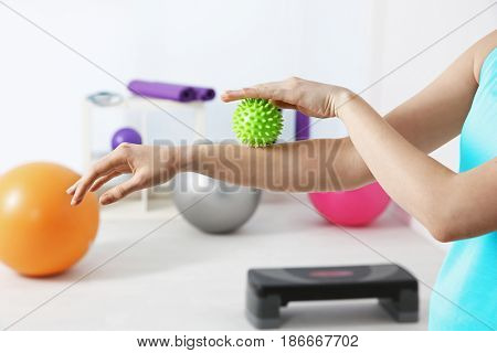 Hands of woman doing exercises with rubber ball in clinic