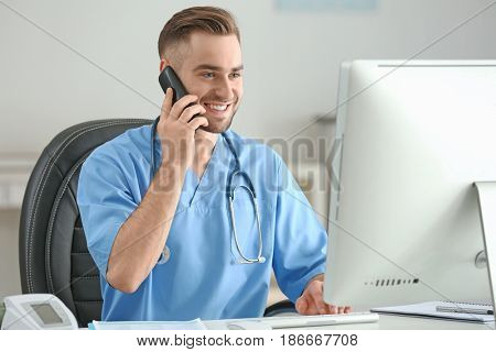 Young medical assistant talking by telephone while working in office