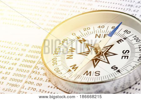 Conceptual compass on account book background for finance Future financial direction concept.