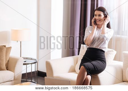 On the phone. Joyful delighted brunette woman putting her cell phone to her ear and smiling while having a phone conversation
