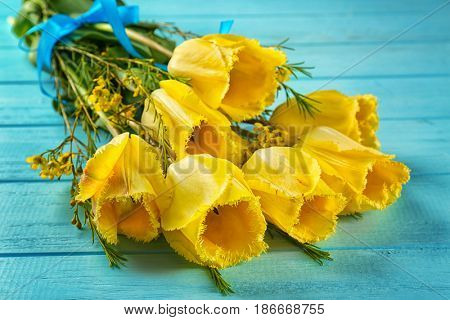 Bouquet of beautiful flowers on color wooden background, closeup
