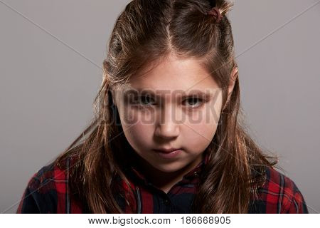 Serious ten year old girl looking to camera, head and shoulders