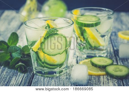 Lemon And Cucumber Detox Water On Blue Colored Wooden Background.