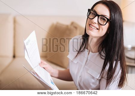 Wonderful mood. Cheerful smart nice businesswoman smiling and looking at you while having some documents in her hands