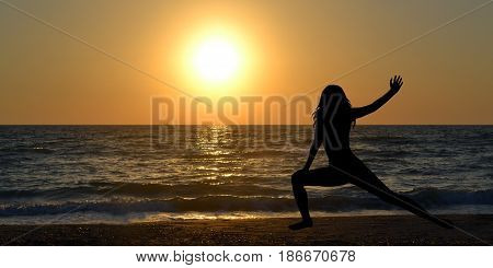 Woman silhouette in a yoga pose on the beach at sunrise