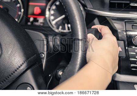 Driver handling the car's direction indicator. Car interior.