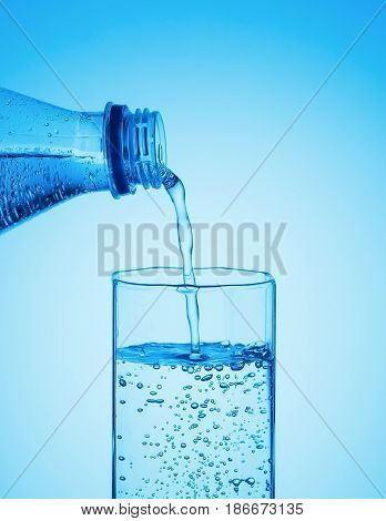Pure drinking carbonated water pours from a bottle into a glass