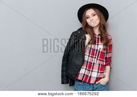 Portrait of a young stylish girl wearing plaid shirt and chewing bubble gum isolated over gray background