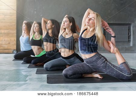 Women in yoga class, mermaid pose stretching. Girls do exercises. Healthy lifestyle in fitness club