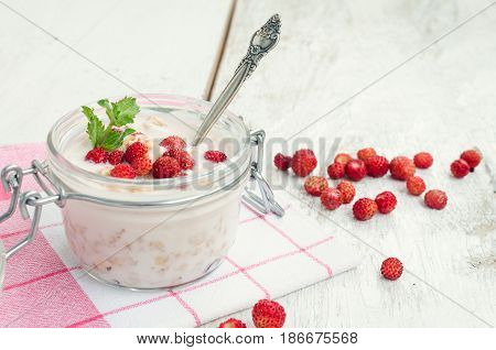 Fresh yoghurt with wild strawberries and granola served in a glass jar with mint leaves on white wooden table with striped red napkin. Healthy summer breakfast concept. Selective focus. Copy space.