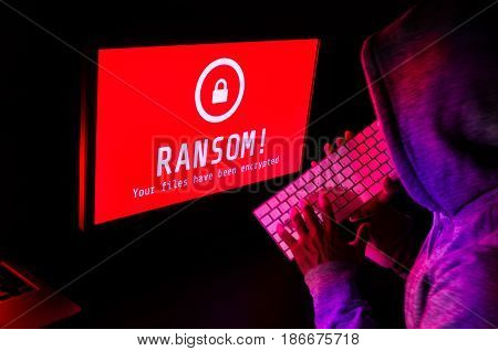 Computer screen with ransomware attack alert in red and a hacker man keying on keyboard in a dark room ideal for online security failure and digital crimes long exposure selective focus