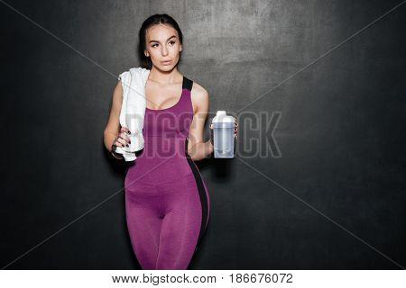 Portrait of a sporty young woman in tracksuit holding water bottle and looking away isolated over black background