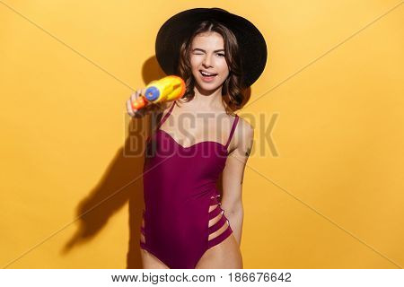 Portrait of a young playful girl in beachwear pointing water gun and winking isolated over yellow background
