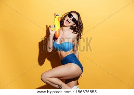 Image of smiling young woman in swimwear isolated over yellow background holding toy water gun. Looking at camera. poster
