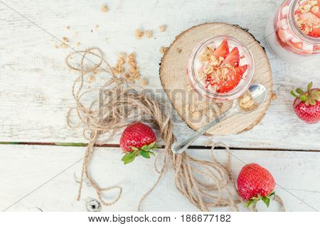 Fresh milk yoghurt with strawberries marshmallow and granola served in a glass jars on white wooden table. Healthy summer breakfast concept. Top view.