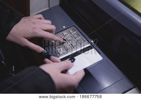 Close up of female hand holding ATM card and entering security code