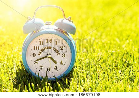 summer vacation time - alarm clock in green grass on sunny day