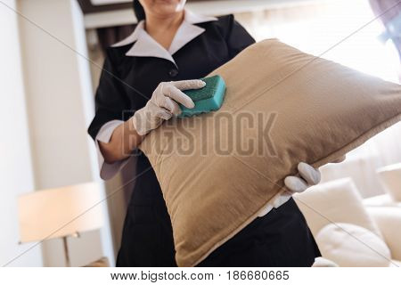 Sofa cushions. Close up of a sofa cushion being in the hands of a professional nice positive chambermaid while cleaning it