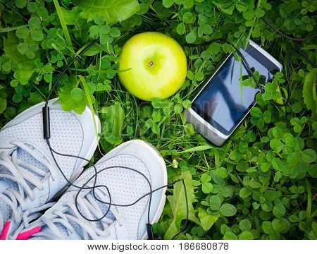 Sneakers and smartphone with headphones and apple on fresh green grass. Sports in the open air. Top view