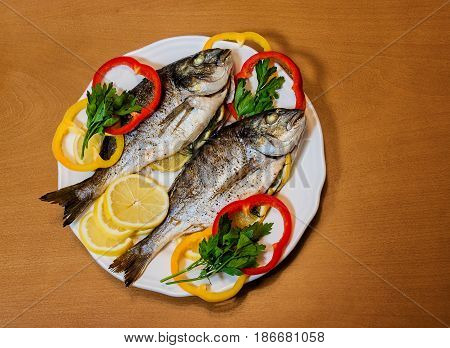 Baked dorado with lemon on wooden background