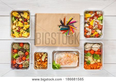 Daily meals plan with healthy food delivery. Salads, meat anf fruits top view on white wood