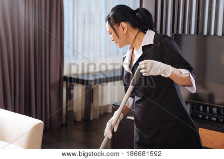 Hard working staff. Nice pleasant delighted chamber maid looking at the floor and cleaning it while working in the hotel room