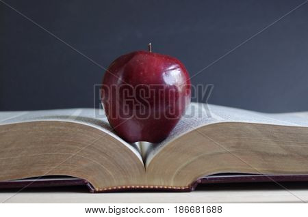 red apple sitting on open text book