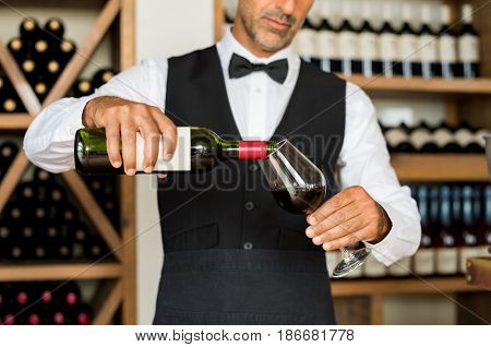 Close up of sommelier hands pouring red wine in a glass. Mature man in waistcoat pouring red wine in glass. Bartender serving wine in glass with shelfs of bottles behind.