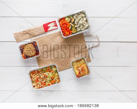 Healthy daily meals delivery in foil containers on white wood. Vegetables, meat and salads. Top view, flat lay