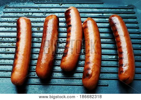 Sausages with brown grill marks in a grill pan