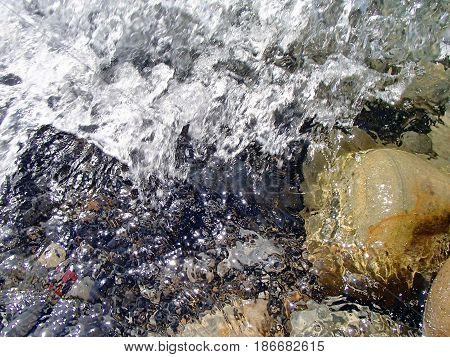 Colorful stones under transparent water. Shallow water, sun glare. Sea foam. Summer, Black Sea near South Ozereyevka, Novorossiysk, Russia. Low DOF photography.