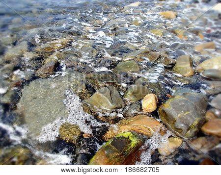 Colorful stones under transparent water. Low DOF photography. Shallow water, sun glare. Sea foam. Summer, Black Sea near South Ozereyevka, Novorossiysk, Russia.