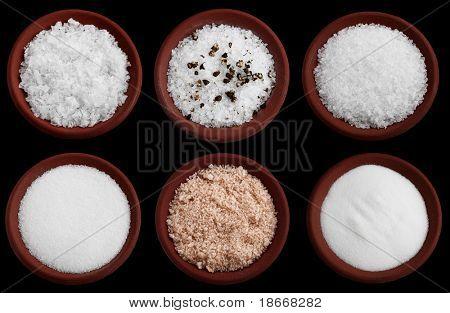 six terracotta plates with different salt - flakes sea salt, coarse sea salt with crashed black pepper, coarse sea salt, fine sea salt, smoked flaky sea salt, table salt, Isolated on black