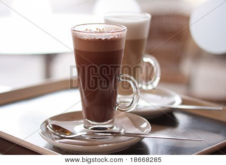 Hot chocolate in a tall class with Coffee Latte on Cafe background
