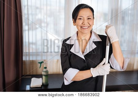 Feeling positive. Happy delighted Asian chambermaid smiling and holding a mop while doing the cleaning up