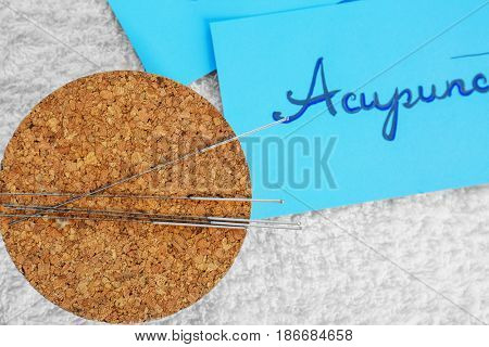 Coaster with acupuncture needles and sheet of paper on fabric background