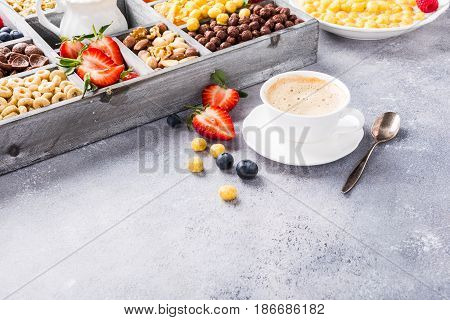 Healthy breakfast with coffee, variety of cold quick cereals and berries in old gray wooden box, selective focus. Copy space.