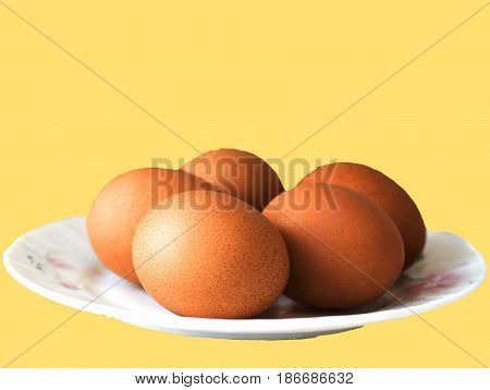Eggs lie on a ceramic saucer isolated in yellow background