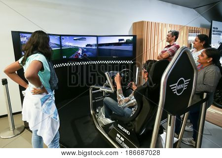 MUNICH GERMANY - MAY 6 2017 : People trying out the BMW car driving simulator in the BMW Welt exhibition center next to the BMW Museum in Munich Germany.