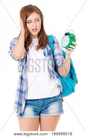 Beautiful student teen girl with backpack and alarm clock, isolated on white background