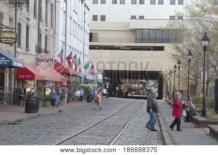 Savannah, Georgia USA - January 20, 2017: People exploring the waterfront Savannah Riverwalk and tunnel passageway that divides it. Also called River Street Home the Riverwalk is a popular destination for locals and tourists