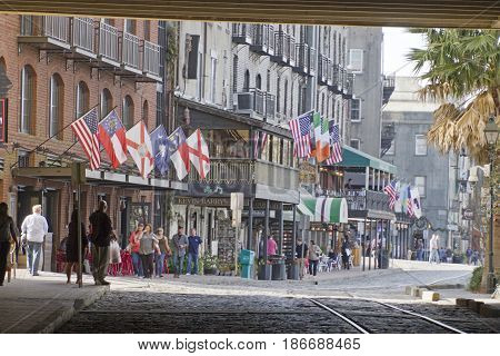 Savannah Georgia USA - January 20 2017: The waterfront Riverwalk as seen from under the tunnel like passageway that divides the street. Also called River Street Home the Riverwalk is a popular destination for locals and tourists with its cobblestone stree