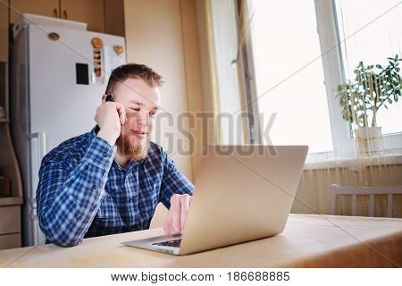 Young Businessman Looking At A Chart That Is Lying On His Laptop With Deep Concentration While On Hi