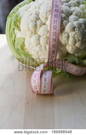 Raw cauliflower with a tape measure on the wooden background