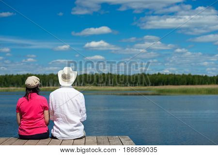 Man and woman are sitting on the shore and looking at a beautiful lake