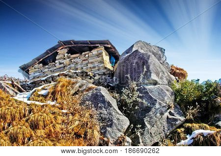 Small  house on a in the rock / mountains with a beautiful sky in the background and sun rays