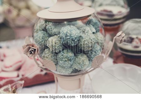 Confectionery sale. Cconut candies or cakes, blue balls in glass jar closeup