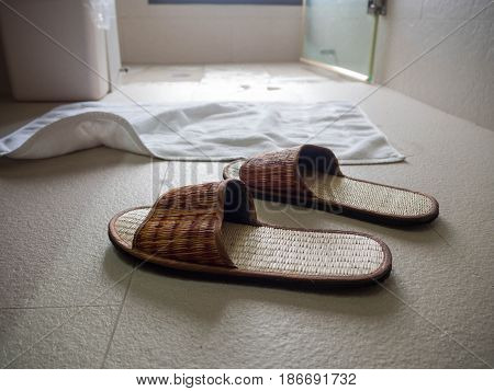 Slippers on the floor in the bathroom the back is a white cloth put in front of the shower