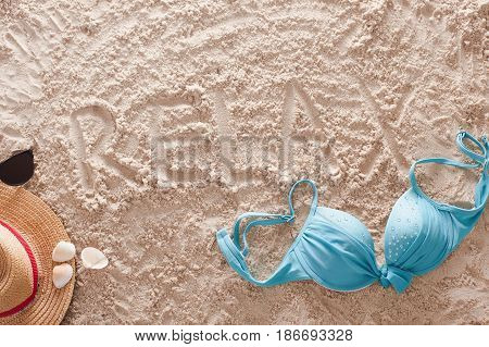 The word Relax written in a sandy tropical beach